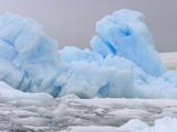 Blue Iceberg Floating Amid Ice Chunks