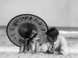 1920s Romantic Couple Looking At One Another Laying Face To Face Under Parasol On Sandy Beach