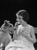 1920s 1930s Girl Eating Cookie With Dog