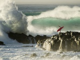 Surf Crashing near Surfer on Boulders