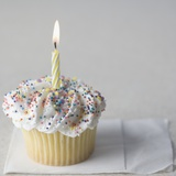 Cupcake with one candle and napkin
