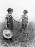 1930s 1940s Boy Girl Holding Hands Walk Down Grassy Hill Wearing Overalls Carrying Straw Hat