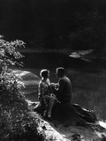 1920s 1930s Romantic Couple Sitting By Stream In Soft Moody Afternoon Sunlight