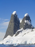 Snowcapped Pinnacles Rising from Coast