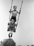 1930s Two Boys Sitting Standing On Playground Swing