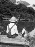1920s 1930s Farm Boy Wearing Straw Hat And Overalls Sitting On Log With Spotted Dog Fishing In Pond