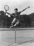 1930s Teenage Boy Tennis Player Jumping Net With Racket In Hand
