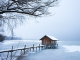 Snow covered pier and boat house at Lake Starnberg