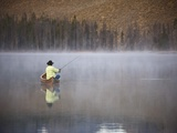 Man fishing on foggy lake