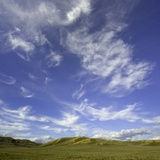 Lofty cumulus and cirrus clouds over sagebrush prairie