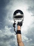 Football player holding helmet in air