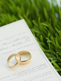 Wedding rings and marriage certificate on grass
