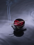 Burning incense on top of bowl of petals