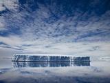 Tabular iceberg reflected in still water