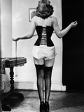 Young Woman Lacing Her Corset Papier Photo par Bettmann