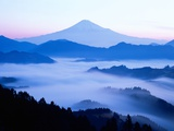 Distant view of Mount Fuji silhouetted against blue sky