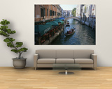A Gondolier Passes a Restaurant on a Canal in Venice  Italy
