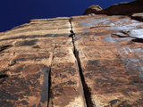 A Rock Climber Tackles An Overhanging Crack in a Sandstone Wall on the Cliffs of Indian Creek  Utah