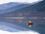 Flat Calm Loch Levan With Reflections of Snow-Capped Mountains and Small Red Fishing Boat  Scotland