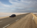 Chott El Jerid  a Flat Dry Salt Lake  and Automobile on Highway Between Tozeur and Kebili  Tunisia