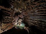A caver explores Hang Ken with its shallow pools