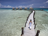 A Woman Walks on a Pier at the Manihi Pearl Beach Resort