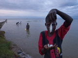 A Boy Nets Small Species of Fish From Lake Albert