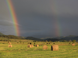 A Double Rainbow Appears over Hay Bales in Mountain Field