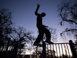 A Teenager Practices a Parkour Move at a Playground