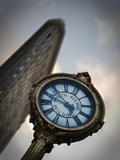 A Large Clock in Front If the Flatiron Building on 5th and Broadway