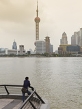 A Man Looking at the Oriental Pearl Tower and Pudong Skyline across the Huangpu River from the Bund