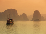 Traditional Boat Sailing Through Limestone Archipelago at Sunset  Ha Long Bay  UNESCO World Heritag
