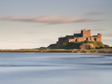 Bamburgh Castle Bathed in Golden Evening Light Overlooking Bamburgh Bay with the Sea Filling the Fo