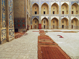 Arched Entrance in a Row of Historic Building with Carpets Lying on Courtyard  Bukhara  Uzbekistan