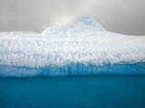 Blue Iceberg Floating in Dark Sea on Overcast Spring Day