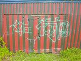 Green Graffiti on Old Garage Door Painted in Red and Green Stripes