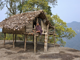 A Man Sits on the Veranda of His Small House  Raised on Stilts  Situated Precariously on the Edge o