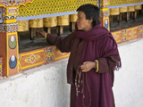 A Woman  Prayer Beads in Hand Spins Brass Prayer Wheels as She Mutters Invocation to Protective Dei