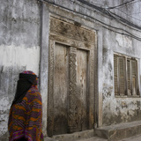 Zanzibar  Tanzania a Zanzibari Women in Traditional Khanga Robes  Passing an Old Wooden Door in St