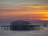UK  England  Sussex  Brighton  Boat Sailing Past Remains of Brighton West Pier at Sunset