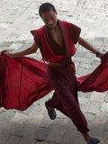 A Young Monk Holds His Red Robes and Runs across Wangdue Phodrang Dzong (Fortress) Courtyard  Massi