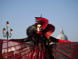 Venice  Veneto  Italy  a Mask in Costume on the Bacino Di San Marco with the Cupola of Santa Maria