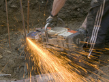 A Builder Cutting Steel Rods
