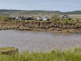 Tourists in Safari Vehicles Witnessing Wildebeest Migration across Mara River
