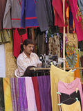 Indian Man Working Outdoors Among Colorful Clothes and Fabrics with a Sewing Machine  Jaisalmer