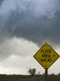 A Road Sign Warns of Flooding on a Rural Road in Kansas as a Tornadic Thunderstorm Spins Above