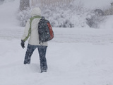 A Pedestrian Walks Through Deep Snow Wearing Cold Weather Clothing During a Winter Storm