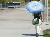 A Woman Wears Loose Fitting Clothing and Carries an Umbrella to Block the Sun During Heat Wave