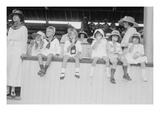 Children Sit on Wall in Front of Stands at the Ballpark and Eat Ice Cream Cones