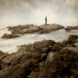 A Lone Man Standing on Large Rocks with the Seas Swirling around Them